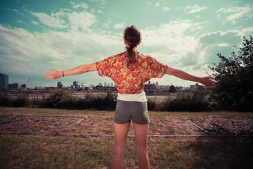 Young woman raising her arms and admiring the view
