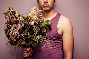 Young man holding bouquet of dead flowers