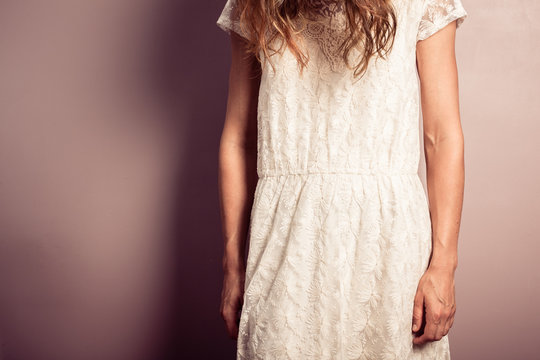 Sad young woman in white dress standing by purple wall