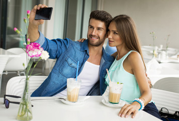 Beautiful couple having fun using smartphone camera