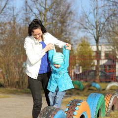 mother doing fitness with little daughter at the playground