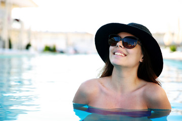 Happy woman standing in swimming pool