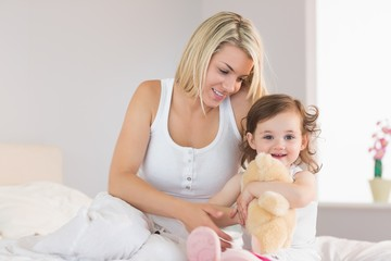 Relaxed mother and daughter sitting on bed