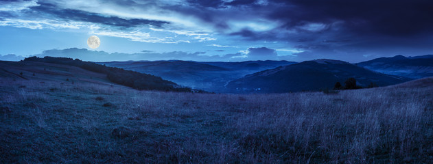 Foto op Canvas Nachtblauw valley in mountains on hillside under sky with clouds at night