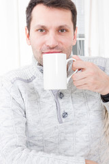 Man Sitting On Chair Drinking Coffee Relaxing At Home