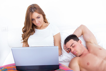 woman relaxing in bed using laptop while husband is sleeping