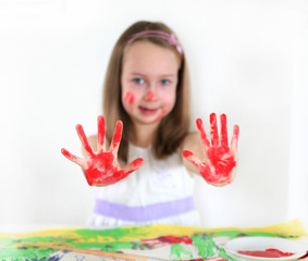 Little girl drawing and demonstrating her art craft work