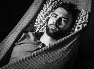 Portrait of young handsome serious man in a hammock.