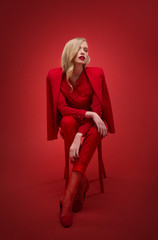 Stylish woman in red suit in studio