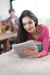 couple at home woman at foreground using digital tablet and man