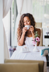 Young woman enjoying smell of coffee