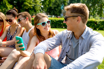 smiling friends with smartphone making selfie