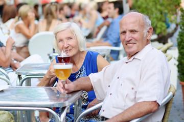 Senior couple enjoying refreshing drinks in outdoors cafe