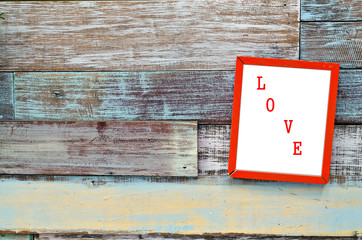 Love red wooden frame hanging on a wooden board