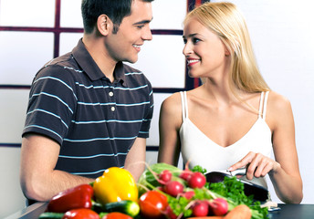 Young attractive happy smiling couple cooking