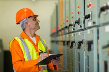 mid age technician writing down machine setting data