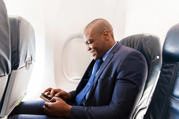 african airplane passenger using smart phone on plane