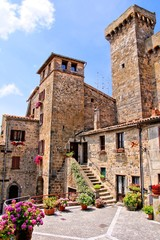 Fotomurales - Medieval square with flowers in a Tuscan village, Italy