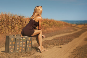 Sexy blonde woman sits on an old suitcase outdoor