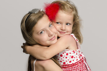 Girl holding in her arms, kissing and having fun with her sister