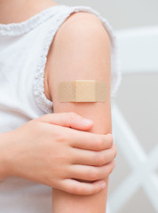 Child arm with an adhesive bandage.