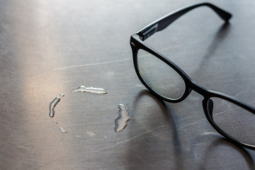 a black frame glasses on standless desk near water stain.