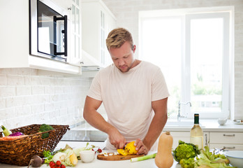 Man cooking at home preparing salad in kitchen