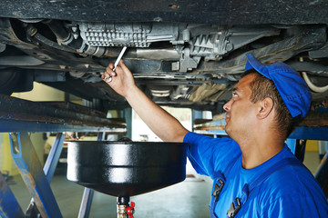 car mechanic replacing oil from motor engine
