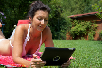 im Gras am Tablet arbeitende Frau