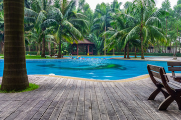 Swimming pool with hut and wooden pool deck in garden of resort