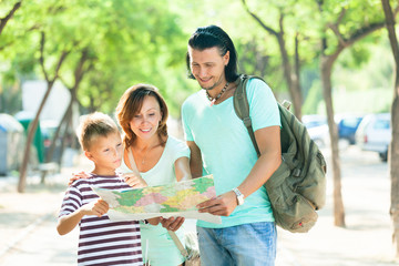 family of three searching way at paper map