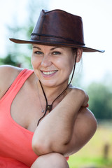 Smiling Caucasian cowgirl in leather hat