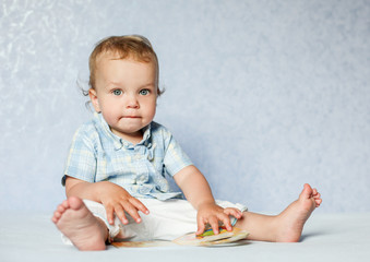 Toddler boy sitting considering the book