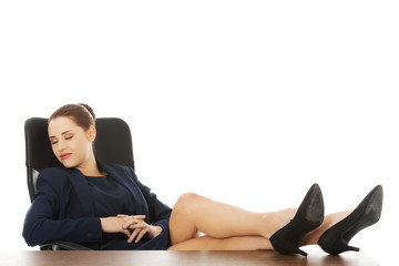 Businesswoman sitting with legs on desk