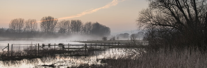 Foto op Plexiglas Grijs Panorama landscape of lake in mist with sun glow at sunrise