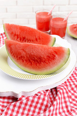 Juicy watermelon on table on brick wall background