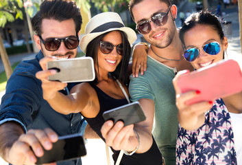 Portrait of group friends taking photos with a smartphone.