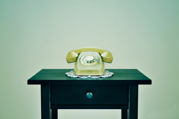 old rotary dial telephone on a table, with a retro effect