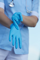 woman doctor wears medical gloves