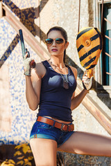 sexy woman wearing sunglasses holding handgun