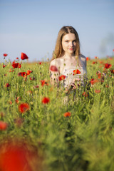 Woman at white dress at poppies field