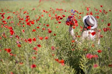 Woman  at dress walk in poppy field