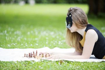 Woman  with mask decide move chess piece