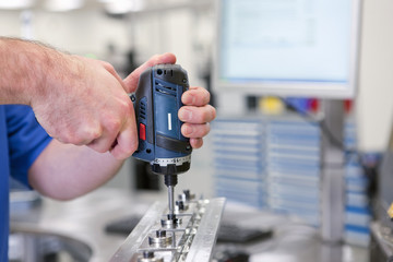 Close up of technician assembling product in hi-tech manufacturing plant