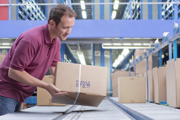 Smiling man packing box on conveyor belt in distribution warehouse