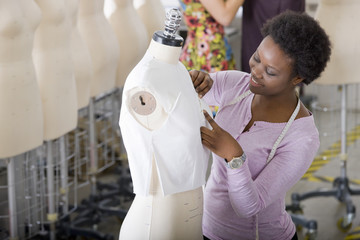 Fashion design student working on garment on mannequin