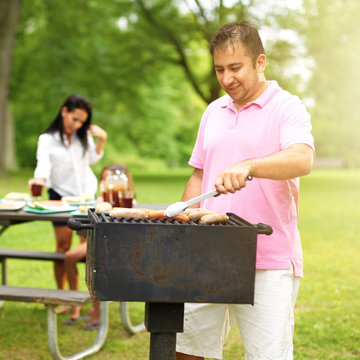 family barbecue - dad grilling with wife and daughter