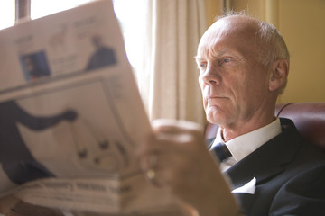 Senior businessman in armchair reading newspaper