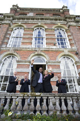 Businessman and woman waving from balcony of manor house by colleagues clapping, low angle view