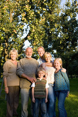 Family of three generations arm in arm in orchard, smiling, portrait